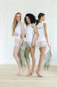 Портрет трех великолепных многорасовых молодых женщин с разными типами кожи. девушки стоят в ряд и смотрят в разные стороны. концепция разнообразных друзей. пальмовая ветвь