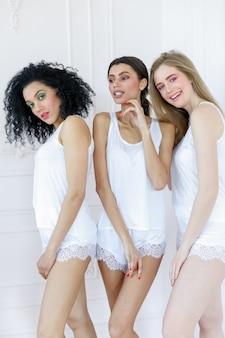 Портрет трех великолепных многорасовых молодых женщин с разными типами кожи. девушки стоят в ряд и смотрят в разные стороны. концепция разнообразных друзей.
