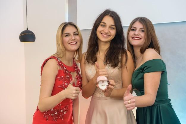 3人の幸せな若い女性の肖像画、ギフトボックスとパーティーのイブニングドレスのクリスマスコンセプト