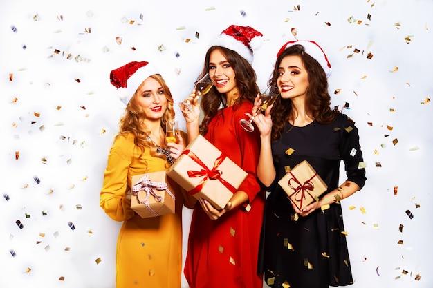 Портрет трех счастливых молодых женщин в шляпе санта-клауса с подарком и бенгальскими огнями.