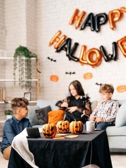 장식된 방에 있는 테이블에 서 있는 동안 할로윈 파티 동안 채팅하는 세 아이의 초상화