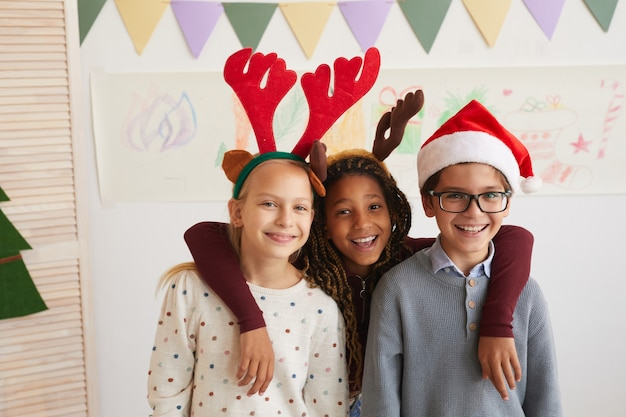 クリスマスの授業を楽しみながら、サンタの帽子をかぶってカメラを見ている3人の子供の肖像画、コピースペース