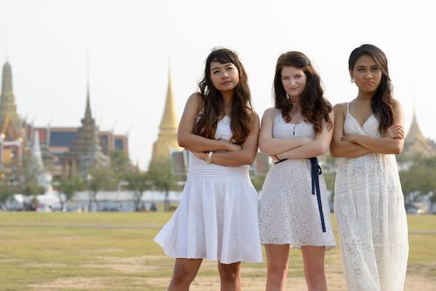 屋外の公園で一緒に友達として3人の多民族の若い美しい女性の肖像画