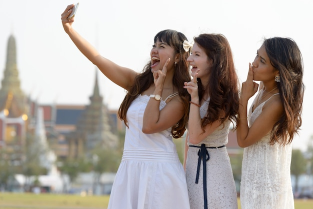 Портрет трех многоэтнических молодых красивых женщин как друзей вместе в парке на открытом воздухе