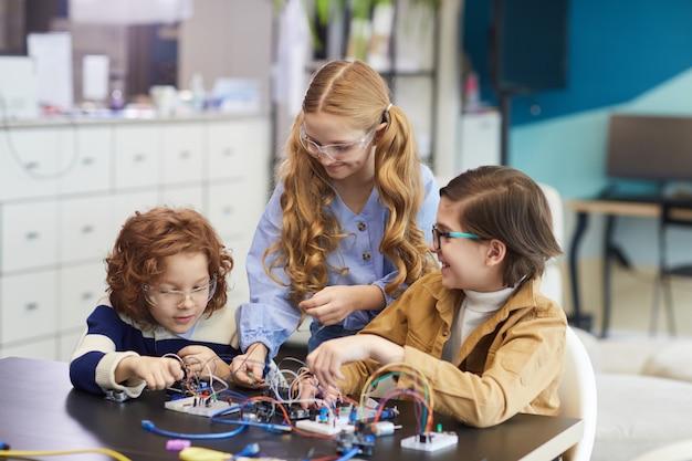 学校の工学の授業でロボットを構築しながら電気回路を実験している3人の笑顔の子供たちの肖像画
