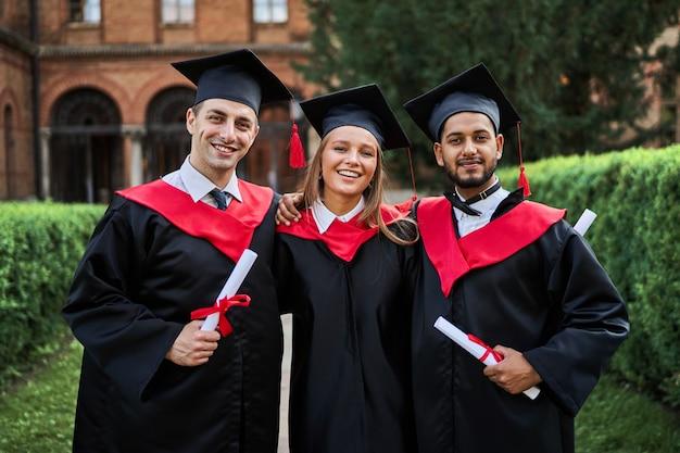 Портрет трех улыбающихся друзей-выпускников в выпускных халатах в университетском городке с дипломом.
