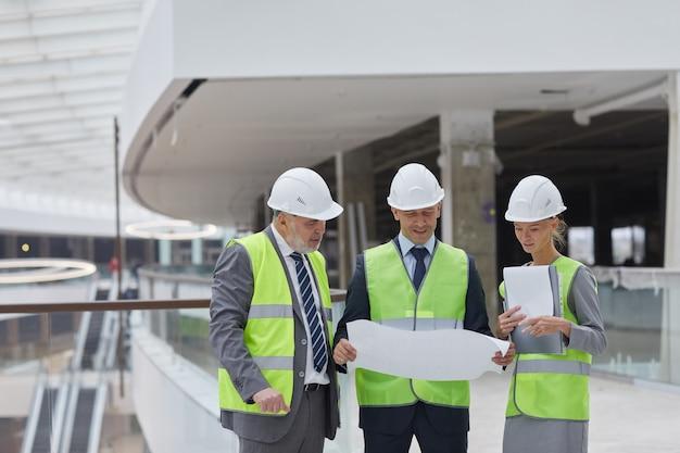 안전모를 착용하고 실내 건설 현장에 서있는 동안 계획을 검사하는 세 명의 성공적인 사업 사람들의 초상화,