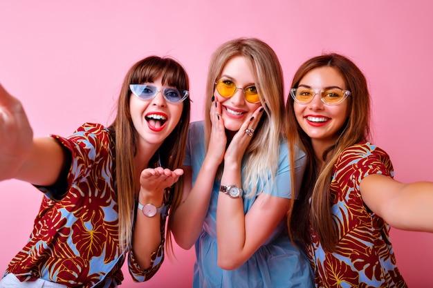 Портрет трех супер восторженных девушек-лучших друзей, блаженная позитивная атмосфера, летняя яркая модная одежда и аксессуары с тропическим принтом, розовая стена, веселые сестры.