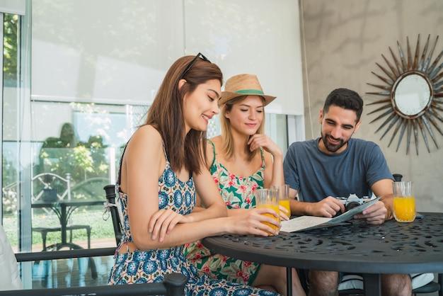 ホテルで時間を過ごし、旅行を計画している3人の旅行者の友人の肖像画。
