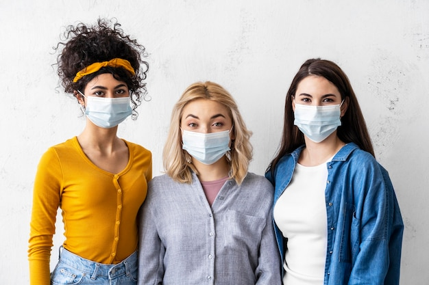 세계 웃음의 날을 위해 의료 마스크를 쓴 세 여성의 초상화