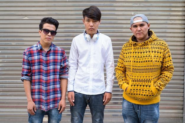 タイ、バンコクの通りの倉庫のドアに立っている3人の若いアジア人の肖像画