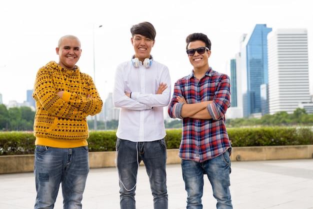 Портрет трех молодых азиатских мужчин вместе отдыха в парке в бангкоке, таиланд
