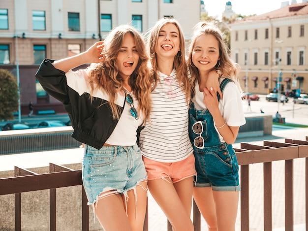 최신 유행 여름 옷을 입고 세 젊은 아름 다운 웃는 hipster 여자의 초상화. 거리에서 포즈 섹시 평온한 여자. 긍정적 인 모델 재미. 포옹과 혀를 보여주는
