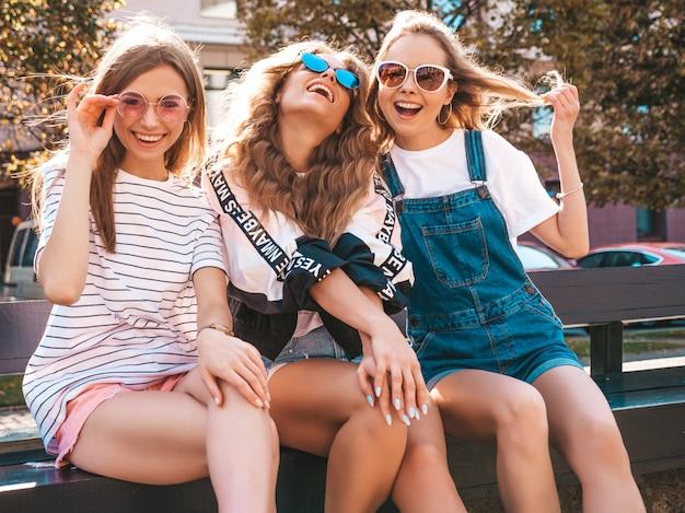 최신 유행 여름 옷을 입고 세 젊은 아름 다운 웃는 hipster 여자의 초상화. 길거리에서 포즈 섹시 평온한 여자. 긍정적 인 모델 선글라스에 재미입니다.