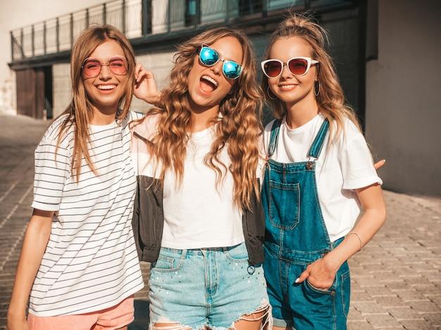 トレンディな夏服の3人の若い美しい笑顔流行に敏感な女の子の肖像画。路上でポーズをとってセクシーな屈託のない女性。サングラスで楽しんでいるポジティブなモデル。 無料写真