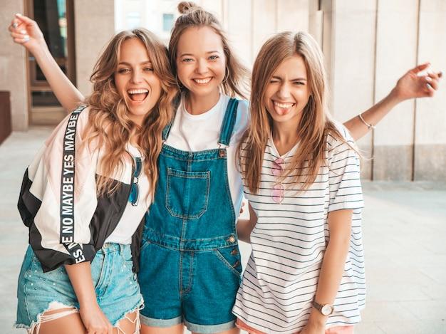 Портрет трех молодых красивых улыбающихся хипстерских девочек в модной летней одежде. сексуальные беззаботные женщины позируют на улице. веселые модели развлекаются