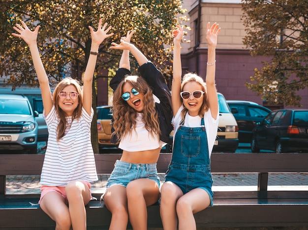 유행 여름 옷에 세 젊은 아름 다운 웃는 hipster 여자의 초상화. 거리에서 벤치에 앉아 섹시 평온한 여자. 긍정적 인 모델 선글라스에 재미입니다.