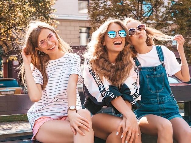 유행 여름 옷에 세 젊은 아름 다운 웃는 hipster 여자의 초상화. 거리에서 벤치에 앉아 섹시 평온한 여자. 선글라스에 재미 긍정적 인 모델