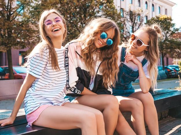 トレンディな夏服の3人の若い美しい笑顔流行に敏感な女の子の肖像画。通りのベンチに座っているセクシーな屈託のない女性。サングラスで楽しんでいるポジティブなモデル