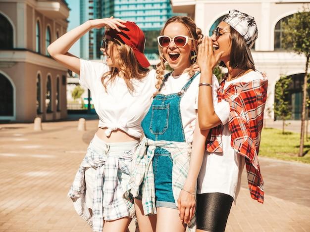 Портрет трех молодых красивых улыбающихся хипстерских девушек в модной летней одежде