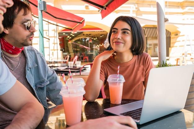 コーヒーショップで屋外に座っているときにラップトップを使用して3人の若い友人の肖像画。友情と技術の概念。