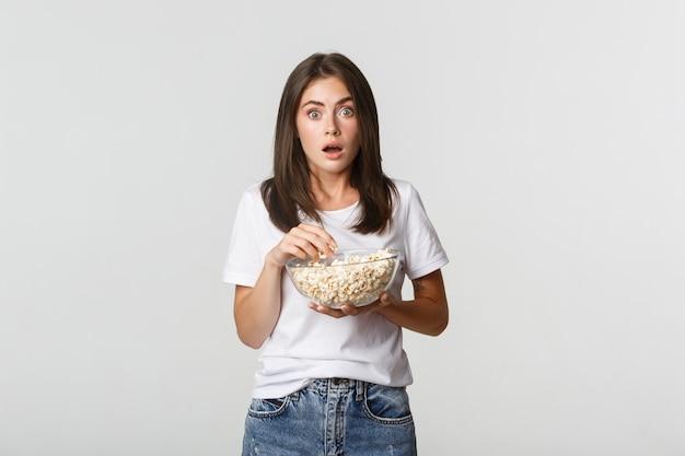 Портрет взволнованной и удивленной молодой женщины, едящей попкорн и смотрящей фильмы или сериалы.