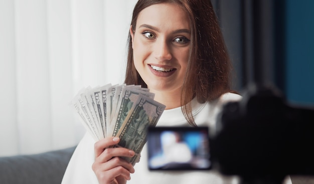 Портрет взволнованной молодой красавицы, снимающей видеоблог, смотрит в камеру и показывает веерообразные доллары