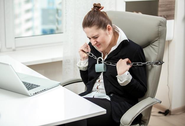 Портрет связанной бизнес-леди, разрывающей металлические цепи