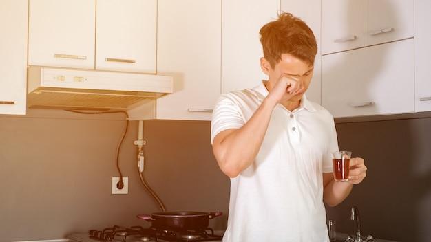 疲れて眠い青年の肖像画は、自宅のキッチンで朝お茶を飲んでいます。彼はあくびをして目をこすり、目を覚まそうとします。平日の早朝。