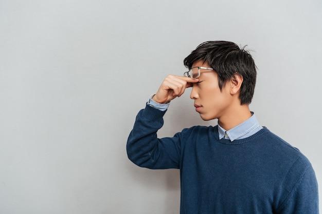 피곤 된 아시아 남자의 초상화입니다. 옆으로 서다
