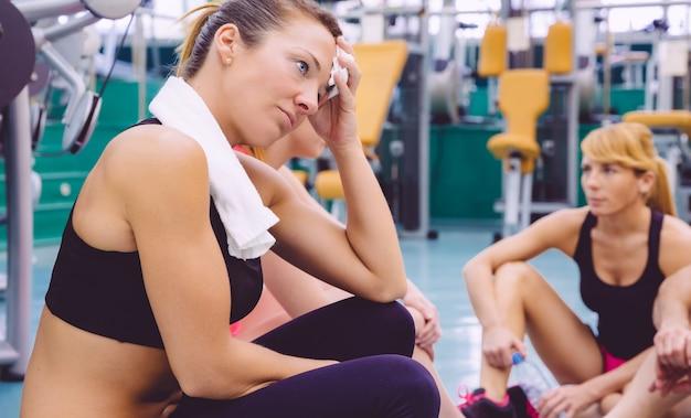 激しいトレーニングの日の後、フィットネスセンターの床に座ってタオルで休んで疲れた美しい女性の肖像画