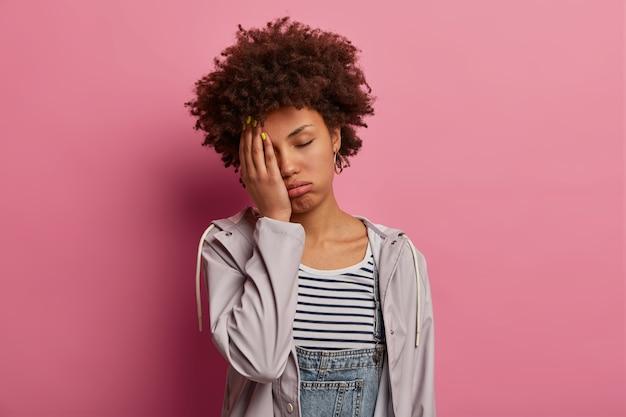 疲れた退屈な若い女性の肖像画は怠惰で無関心を感じ、手のひらで入り江の顔