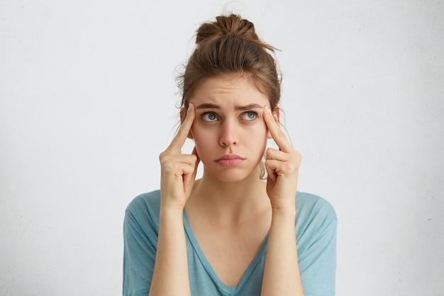 重要な何かを思い出そうとしている欲求不満な表情を見上げている寺院に公正な髪を保持している指で疲れた白人の青い目の女性の肖像画。残りの部分を考えて疲れた女性