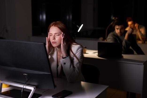 밤에 사무실에서 일하는 빨간 머리를 한 피곤한 백인 여성의 초상화, 힘든 일에 대해 생각하고, pc 컴퓨터를 사용하고, 뒤에서 동료들과 늦게까지 일합니다. 일, 사업