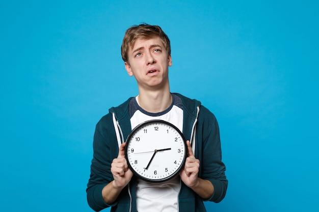 Портрет усталого плачущего молодого человека в повседневной одежде, держащего круглые часы, изолированные на синей стене. время уходит. концепция образа жизни искренние эмоции людей.
