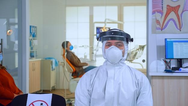 全体的に身に着けているカメラと待合室クリニックの椅子に座っているフェイスシールドを見ている歯科医院の疲れた医者の肖像画。コロナウイルスの発生における新しい通常の歯科医の訪問の概念。