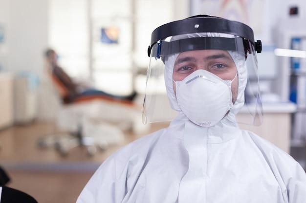 全体的に身に着けているカメラと待合室クリニックの椅子に座っているフェイスシールドを見ている歯科医院の疲れた医師の肖像画
