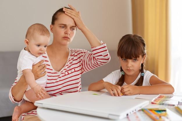 額に手を置いて、赤ちゃんを手に持って、娘が宿題をするのを手伝って、テーブルの部屋でポーズをとって、縞模様のカジュアルなtシャツを着ている疲れた疲れた女性の肖像画。