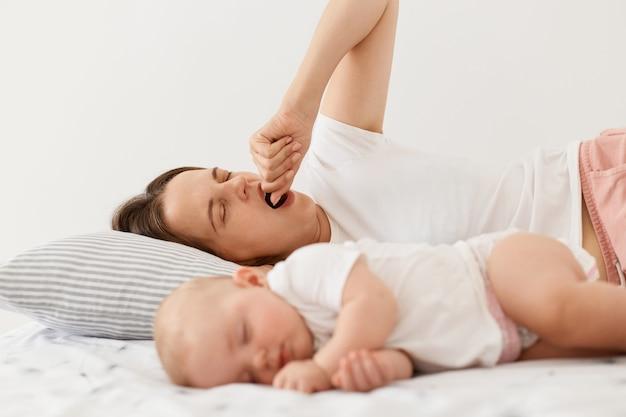 피곤한 지친 어머니의 초상화는 침대에 누워 하품을 하며 열린 입을 주먹으로 덮고 있는 동안 아기가 자고 밝은 방에서 집에서 포즈를 취하는 동안 일찍 일어납니다.