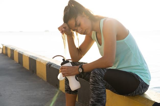 街の屋外で疲れたフィットネス若い女性の肖像画。港の近くの晴れた朝のトレーニングセッションの後に休んでいる若い女性ランナー