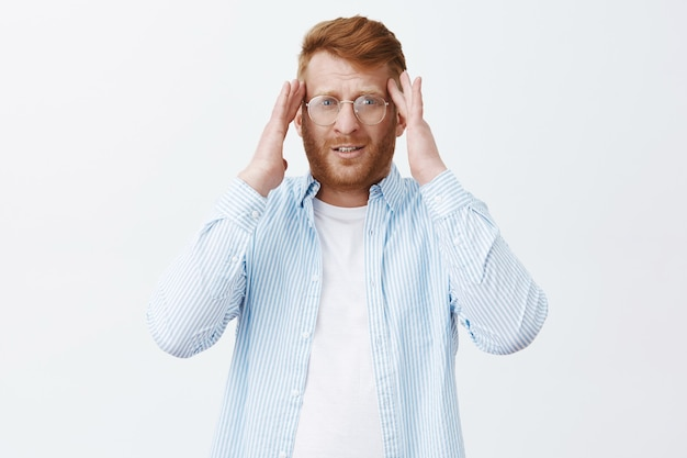 Портрет усталого красивого мужчины-предпринимателя с рыжими волосами и бородой в очках, держащего руки на висках и смотрящего расфокусированным, с головной болью