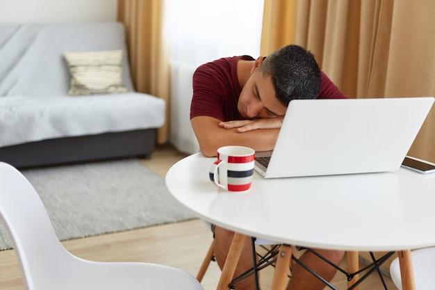 オンラインで作業した後、ラップトップの近くのテーブルで眠りに落ちる疲れた男のフリーランサーの肖像画、カジュアルなスタイルの栗色のtシャツを着て、寝て、彼の手に寄りかかって、窓の近くの明るいリビングルームでポーズをとる。