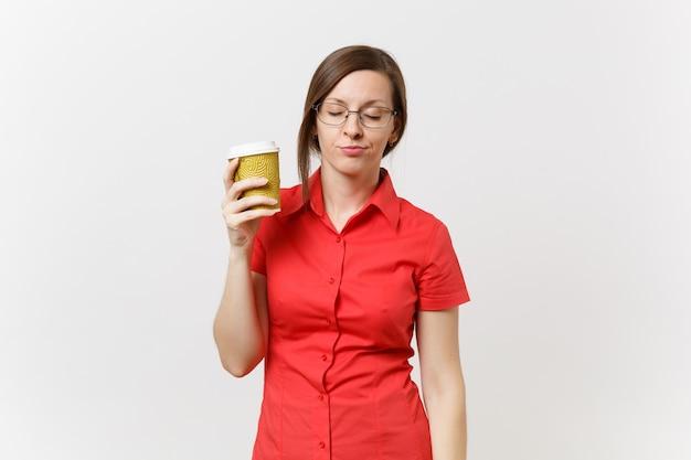 白い背景で隔離の手でコーヒーやお茶のカップを保持している赤いシャツのメガネで疲れた若いビジネス教師の女性の肖像画。高校大学の倦怠感の概念における教育または教育。