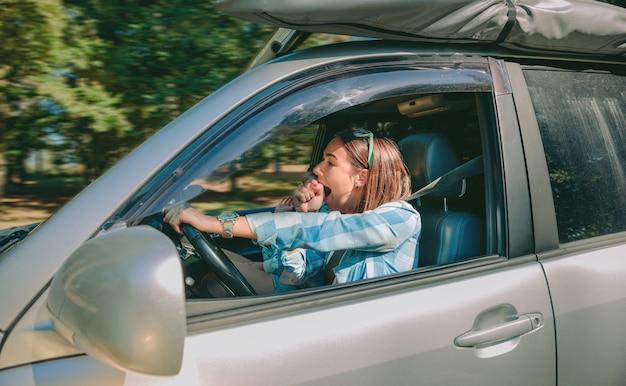車を運転し、長すぎる旅行の後にあくびをする疲れた若い女性の肖像画。道路コンセプトにおけるリスクと危険。