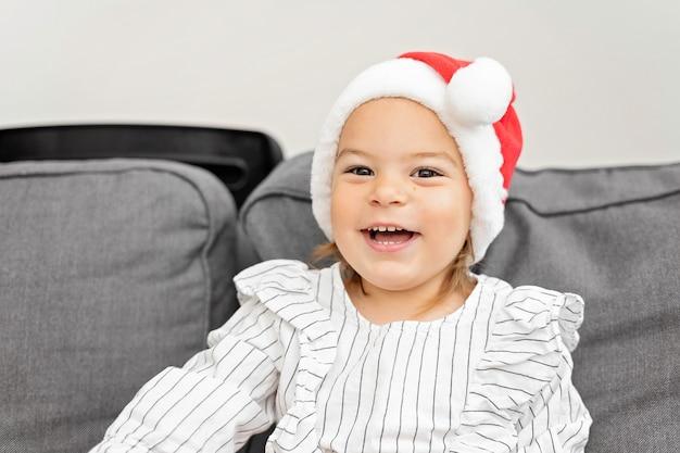 크리스마스에 빨간 모자에 유아 여자의 초상화. 2021 년 새해를 축하하는 행복한 아이