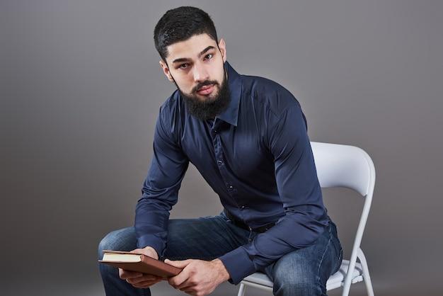 手に本を持って椅子に座っている歯を見せるハンサムなひげを生やした男の肖像画。
