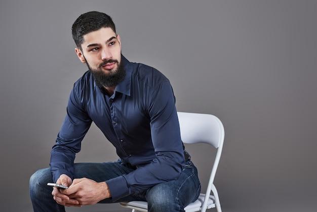 手に電話で椅子に座っている歯を見せるハンサムなひげを生やした男の肖像画。