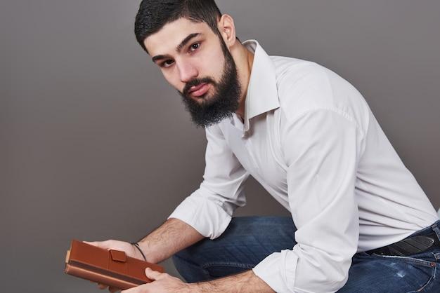 手に本を持つ歯を見せるハンサムなひげを生やした男の肖像画。