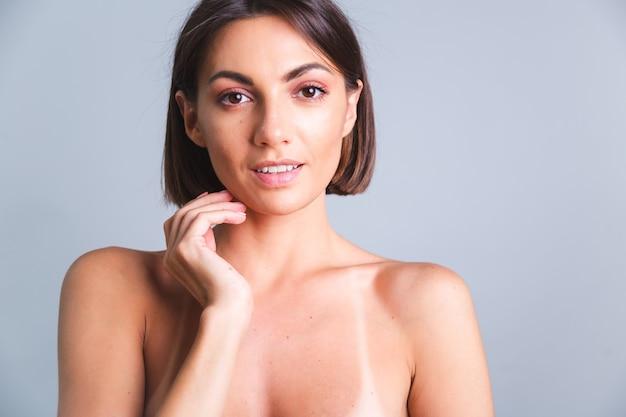 Портрет обнаженной до пояса женщины с макияжем и мягкой нежной загорелой кожей на серой стене