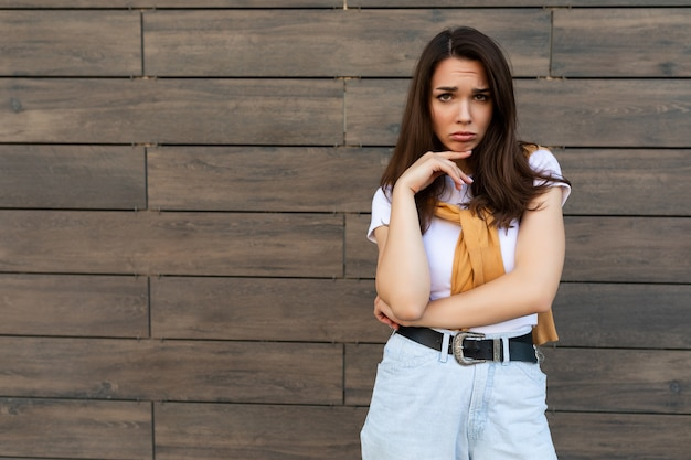 カジュアルな白い t シャツを着た敏感な悲しい動揺の気分を害した若い黒髪の女性の肖像画
